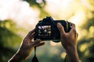 person-holding-dslr-camera-selective-focal-photo-1336926
